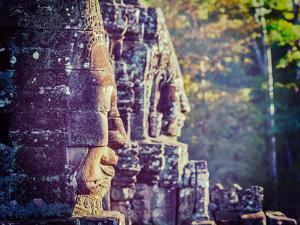 Vintage Retro Effect Filtered Hipster Style Travel Image of Ancient Stone Faces of Bayon Temple, An by f9photos