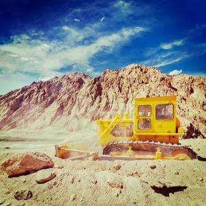 Vintage Retro Effect Filtered Hipster Style Travel Image of Bulldozer Doing Road Construction in Hi by f9photos