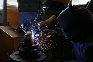 Man Welding Workpiece, Workshop, Flying Sparks by Fact