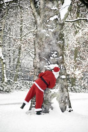 Father Christmas in Snow Behind Tree