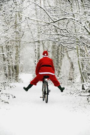 Father Christmas Riding Bicycle in Snowy Woodland Path
