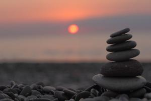 Cairn on the Beach in Front of the Rising Sun by Felix Strohbach