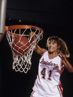 Female Basketball Player Dunking a Ball Through the Hoop
