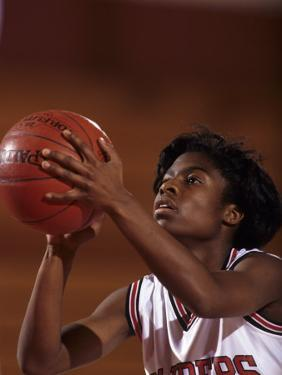 Female High Schooll Basketball Player in Action Shooting a Free Throw During a Game