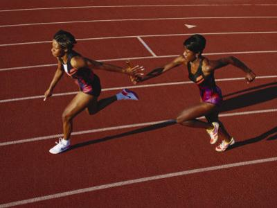 Female Runner Competing in a Relay Track Race