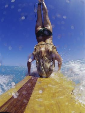 Female Surfer Doing a Headstand on a Surfboard