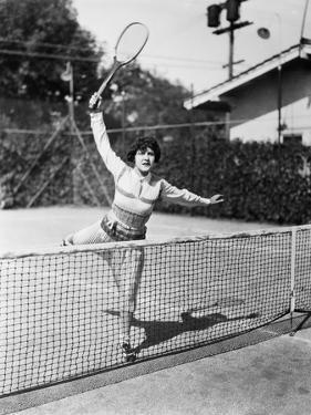 Female Tennis Player Reaching for Shot