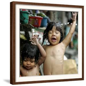 Filipino Children React as They Get a Shower Outside Their Homes