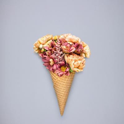 Creative Still Life of an Ice Cream Waffle Cone with Flowers on Grey Background