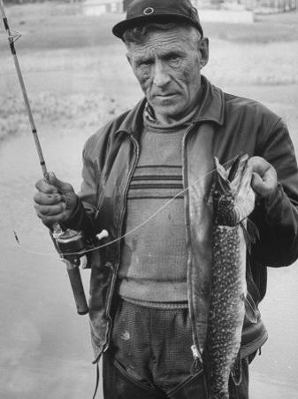 Fisherman Lauri Rapala, Who Handmakes Fishing Lures, with a Fish He Caught