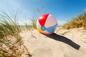 Beach Ball Resting in Sand Dune Concept for Childhood Summer Vacations, Family Holiday and Healthy by Flynt