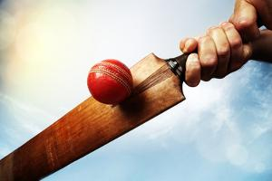 Cricket Batsman Hitting a Ball Shot from below against a Blue Sky by Flynt