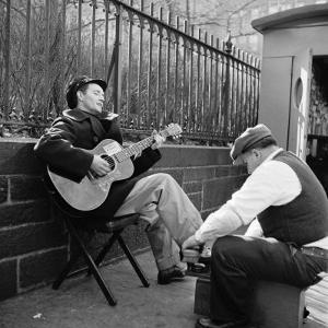 Folk Singer Woody Guthrie Palying His Guitar While Getting a Shoeshine