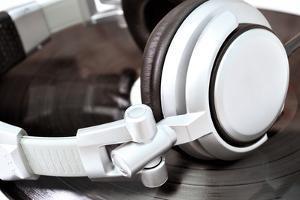 Dj Headphones Lying over Black Vinyl by fotosutra.com