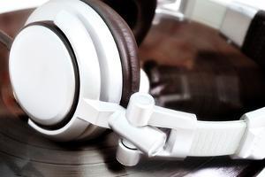 Dj Headphones Lying over Old Vinyl by fotosutra.com