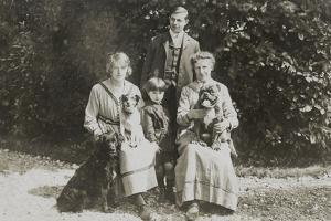 Four People and Three Dogs in a Garden