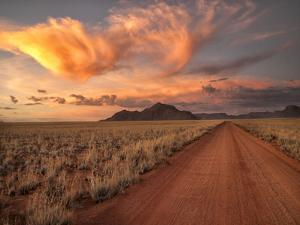 Dirt Road in the Desert at Sunset with a Colorful Sky, Tiras Mountains, Namibia by Frances Gallogly