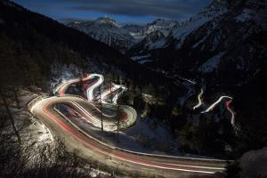 Car lights on the curvy Maloja Pass road at night, Maloja Pass, Engadine, Province of Graubunden, S by Francesco Vaninetti