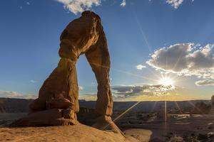 Delicate Arch with sun and clouds at golden hour, Arches National Park, Moab, Grand County, Utah, U by Francesco Vaninetti