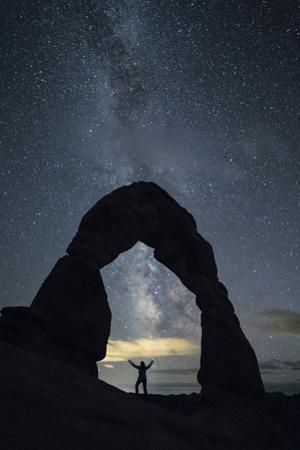Milky Way and person under Delicate Arch, Arches National Park, Moab, Grand County, Utah, United St by Francesco Vaninetti