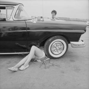 "All-Girl ""Dragettes"" Hotrod Club Working on Car Engine with Children, Kansas City, Kansas, 1959 by Francis Miller"