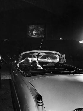 Young Couple Cuddling as They Watch a Movie at Drive in Theater by Francis Miller