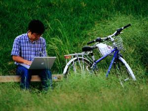 Man Using Laptop Computer Beside His Bicycle Near Kamogawa River, Kyoto, Japan by Frank Carter
