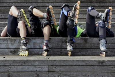 Four Skaters Enjoy the Sunny Weather During a Break at the Riverbank of the Rhine in Mainz