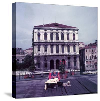 Heiress Peggy Guggenheim Sunbathing on Terrace of Venier Dei Leoni Palace on Grand Canal in Venice