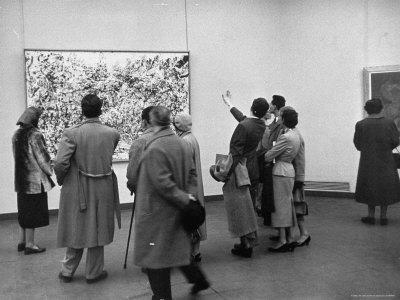 People Looking at a Painting by Artist Jackson Pollack at an American Art Show