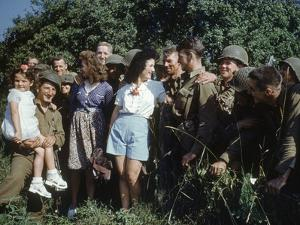 U.S. Soldiers Gather around a French Girl Near Avranches, France, August 1944 by Frank Scherschel