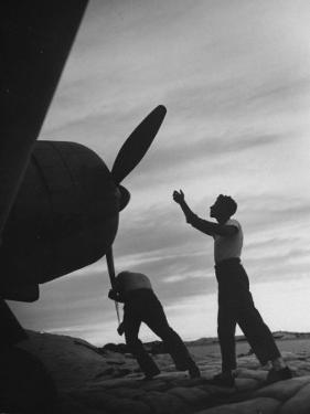 US Marines Pushing Through the Props of Bomber at US Naval Base on Midway Island by Frank Scherschel
