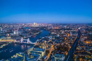 High view of London skyline at dusk along the River Thames from Tower Bridge to Canary Wharf, Londo by Fraser Hall