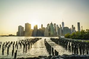 Lower Manhattan skyline across the East River at sunset, New York City, New York, United States of  by Fraser Hall