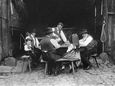 Alsatian Family Sitting at a Table in a Barn at Mietesheim, c.1900 by French Photographer