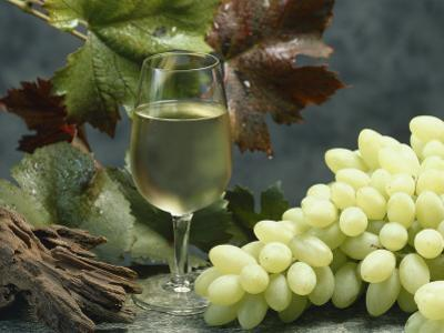 Close-Up of a Glass of White Wine with a Bunch of Grapes by G. Cigolini