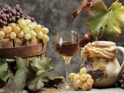Close-Up of a Glass of Wine with a Bunch of Grapes by G. Cigolini