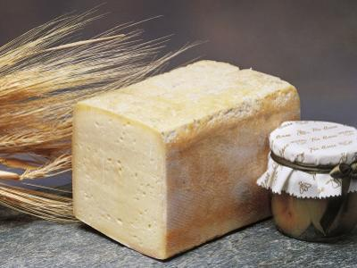 Close-Up of Cheese (Tilsit Cheese) with Wheat and a Covered Jar by G. Cigolini