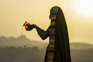 Ahir Woman in traditional colorful cloth pouring water at sunset, Great Rann of Kutch Desert, India by G&M Therin-Weise