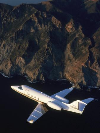 Lear Jet in Flight Over Mountains by Garry Adams