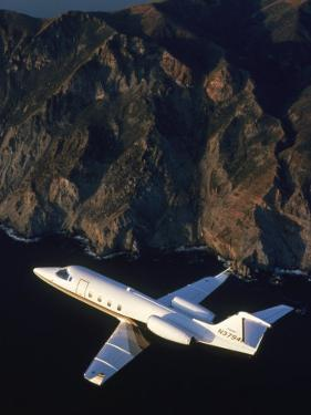 Lear Jet in Flight Over Mountains by Garry Adams