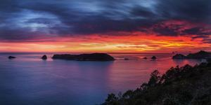 A Fiery Dawn Sky Breaks Beyond the Islands Off the Coromandel Peninsula, Waikato, North Island by Garry Ridsdale