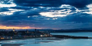 Looking across Bay to St. Andrews Harbour and Pier with Sun Setting Beyond City as Dusk Falls by Garry Ridsdale