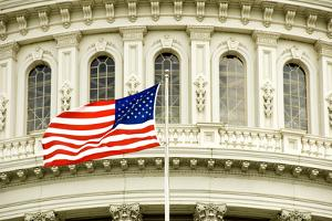 The Flag of the USA Flying in Front of the Capitol Building in Washington, Dc. by Gary Blakeley