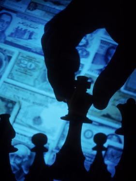 Hand Holding Chess Piece in Front of Currency by Gary Conner