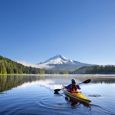A Woman in a Sea Kayak Paddles on Trillium Lake, Oregon, USA