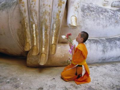 Novice Buddhist Monk Kneeling Beneath the Phra Atchana Buddha Statue, Sukhothai Province, Thailand by Gavin Hellier