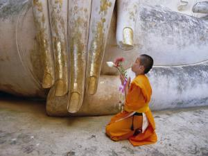 Novice Buddhist Monk Kneeling Beneath the Phra Atchana Buddha Statue, Sukhothai Province, Thailand by Gavin Hellier