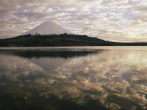 View of Snowcapped Payachata Volcano and a Cloudy Twilight Sky Mirrored in the Lake by George F. Mobley