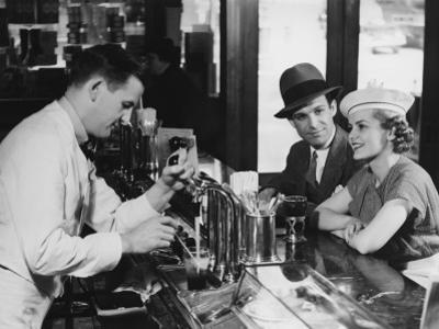 Bartender Pouring Beer For Young Couple in Bar by George Marks